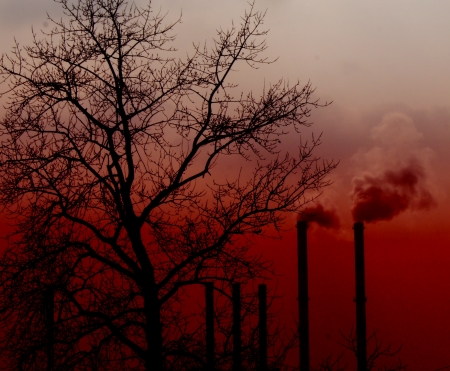 Air pollution by smoke coming out of two factory chimneys on sunset  photo