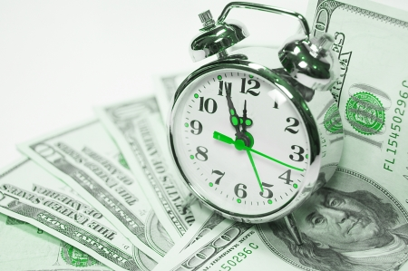 economic revival: Retro styled alarm clock covered pile of money isolated on white  Time is money concept