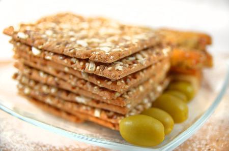 pretzel stick: salty sticks with sesame and poppy seeds Bread sticks or Pretzel stickslinen tiles and olives Stock Photo