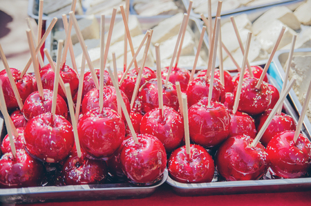 Delicious red candy apples covered with colorful sprinkles