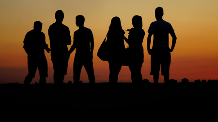 silhouette of few people in sunset summertime Stock Photo