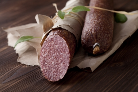 Salami on paper on dark wooden table photo
