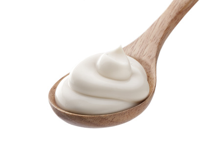 Sour cream in wooden spoon isolated Фото со стока