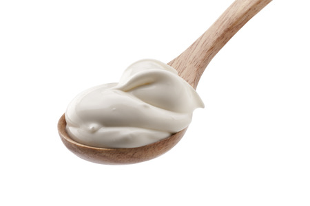 Sour cream in wooden spoon isolated 版權商用圖片