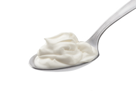 Sour cream in spoon on white background