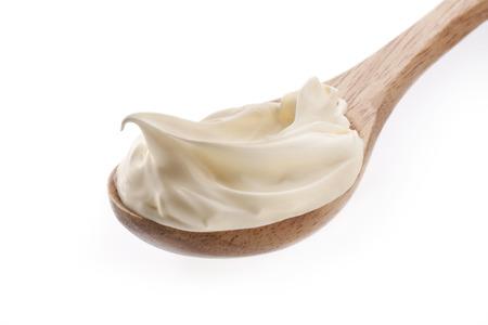 La crème fraîche dans une cuillère en bois isolé