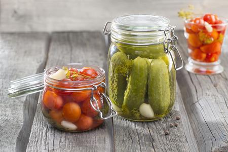 Homemade pickles Cucumbers, Tomatos, Custard squash in brine with garlic, dill and horseradish on woodboard