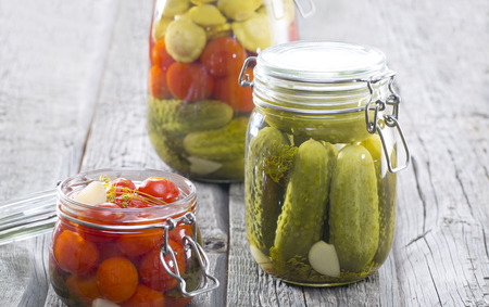 Composition with jars of pickled vegetables on wooden tables. Marinated food
