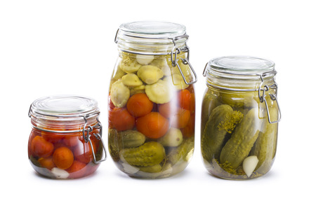 Jars of pickled marinade vegetables tomato, cucumbers and squash isolated on white. Marinated food