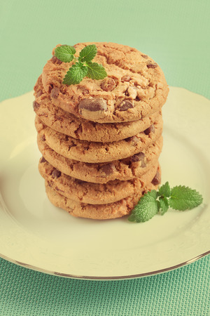A heap of chocolate chip cookies on a white plate with blue background retro. Vintage look.