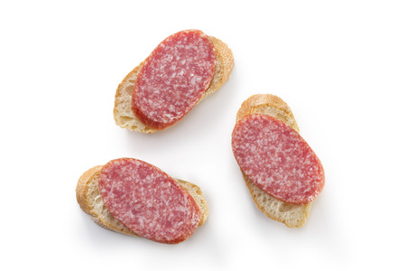 Open sandwiches canapes with salami salami on white background overhead
