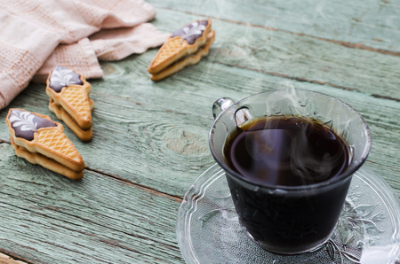 Cup of coffee with cookies on old turquoise wooden board. Selective focus. Foto de archivo