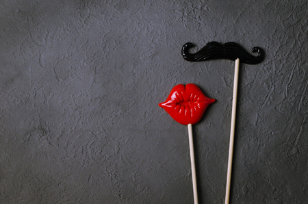 Photo booth props mustache lips on dark stone board background. Valentines or anniversary conception.