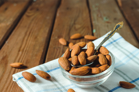 Almonds in a glass bowl on grained wood background. Selective focus. Copy space.