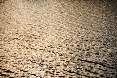 Water surface in the light of the setting sun. Abstract background.