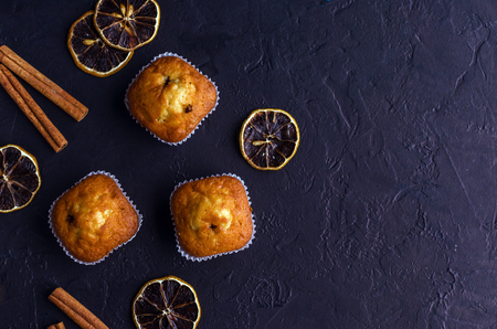 Sweet muffins with on dark textured background. Top view. Copy space.