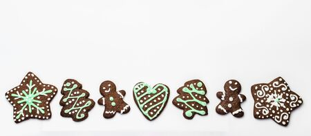 Gingerbread cookies on white background. Snowflake, star, man, heart shapes.