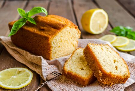Lemon pound cake on rustic wooden background with lemon. Selective focus