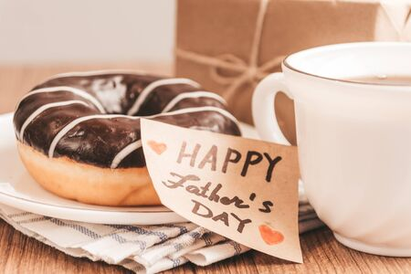 Gift box with a tag, cup of coffee or tea and chocolate donut. Father's day or birthday concept. Selective focus.
