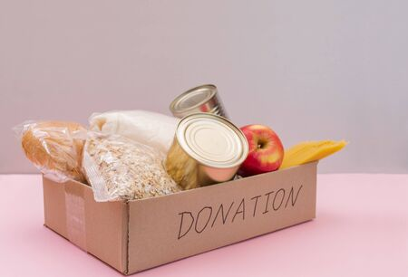 Donation box. Crisis food. Food in a donation cardboard box. Pink background. Space for text. Zdjęcie Seryjne