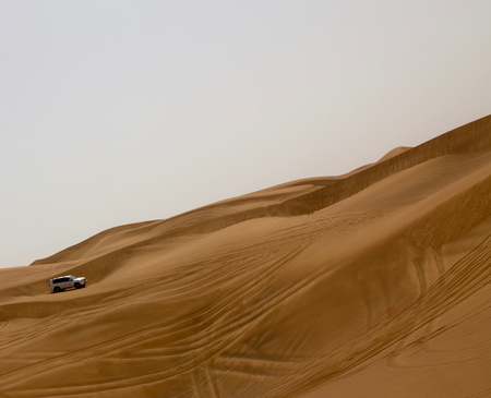 go up: A car (SUV) trying to go up a steep slope in a desert in Dubai, UAE