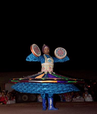 bailarinas arabes: DUBAI, UAE - 20 de abril de 2012: Un ciudadano local que realiza danza popular tradicional en la noche como parte de una experiencia en el desierto campamento de safari Editorial