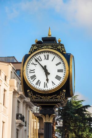 Old Street Clock In Europe. Clock Face With Roman Numerals And Arrows, Cast-iron Column And Gold Decorative Elements. Architecture Element In The Main Square In Batumi.