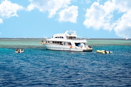 Modern Egyptian Diving Boat In The Sea Near Coral Reef Island. White Marine Pleasure Craft With Tourists In The Red Sea. Entertaining Boat Trip. Calm Blue Sea And Clouds.