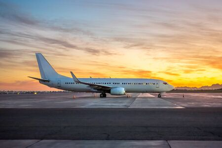 International Airlines Plane Parking Outside The Terminal In The Airport. White Passenger Airplane Side View, Sunset Over The Mountains.