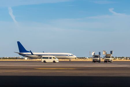 International airlines plane parking outside a terminal in airport. White passenger airplane, side view. Airfield cars, trucks and equipment, aircraft preparation before flight.