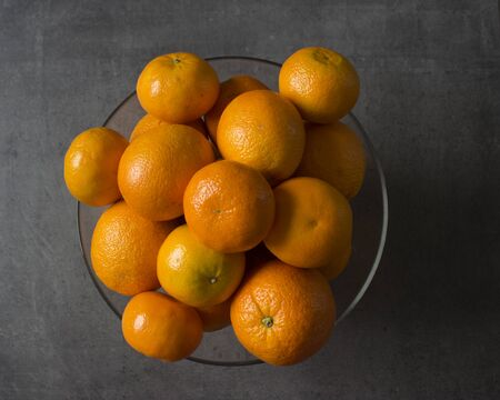 A lot of juicy oranges in glass vase. Fruit texture close up. Fresh summer fruits on dark background with copy space. Stok Fotoğraf