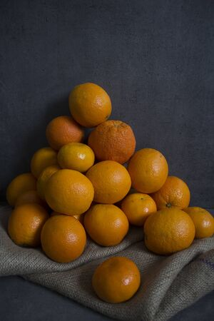 A lot of juicy oranges. Fruit texture close up. Fresh summer fruits on dark background with copy space. Stok Fotoğraf