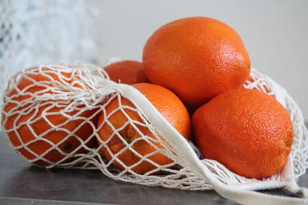 Oranges in white cotton mesh bag. Zero waste concept.
