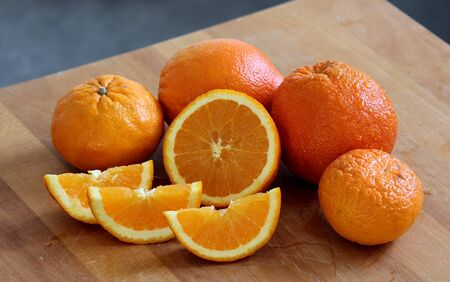 A lot of juicy oranges. Fruit texture close up. Fresh summer fruits on wooden table Stok Fotoğraf