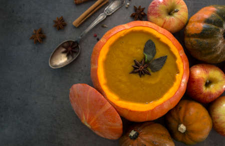 Squash soup in pumpkin bowl on grey textured background with copy space. Top view photo of autumn meal with anise stars, rosemary, cinnamon sticks and silver spoon.