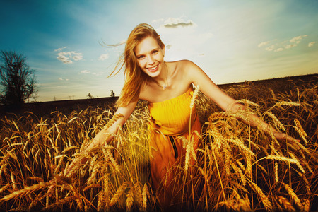 Pretty girl is walking on the wheat field on the sunset background. photo