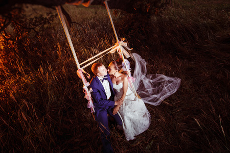 swinging: A beautiful married pair is swinging against the field background.