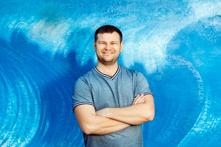 cross armed: A pleased man with squint eyes standing at a blue wall background. Stock Photo