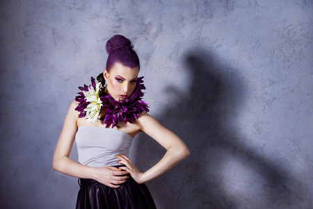 A young model with flowers on her neck standing near the grey wall background. photo