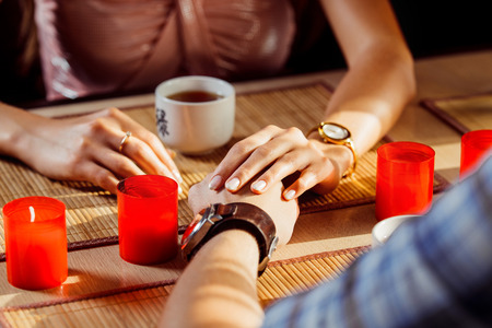 passionately: A loving couple is passionately holding hands at a dating. Stock Photo