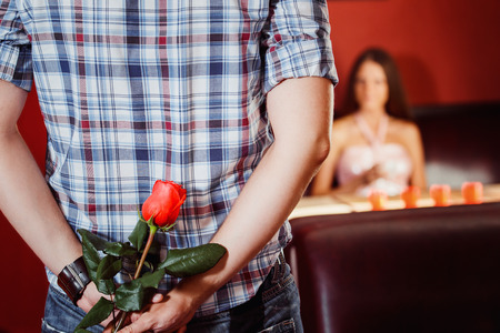Man is hiding a red rose ro make a gift to his girl at their dating.