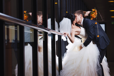 A beautiful kiss of a young newlywed couple near a mirror wall. photo