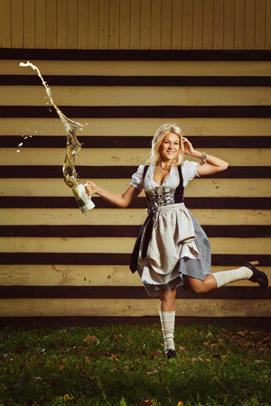 A beautiful young german girl in dirndl clothing is holding a jug of beer. photo