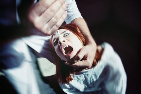 forcing: A man is forcing a woman to take pills holding her head.