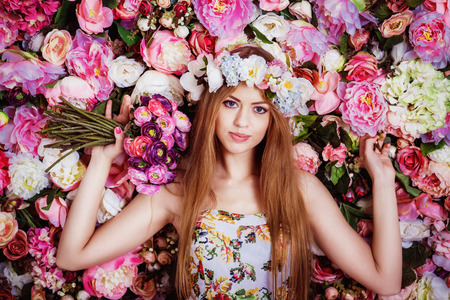 A beautiful young girl with flowers bouquet near a floral wall. Stock Photo