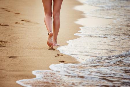Красивая молодая женщина идет по берегу моря, оставляя следы. Фото со стока