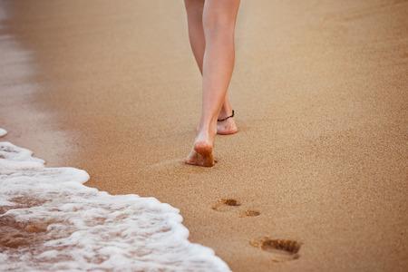 Здоровая молодая женщина идет на желтом песке оставляя следы.