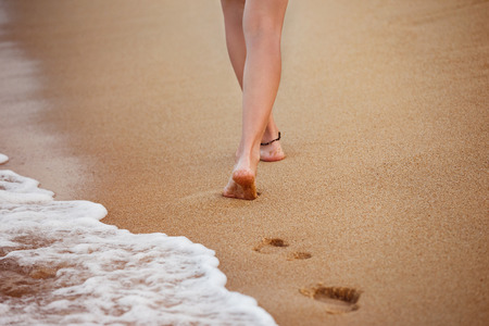 Healthy young woman is walking on the yellow sand leaving footprints.