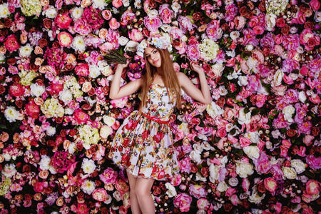 A beautiful young girl with flowers bouquet near a floral wall. Stock fotó