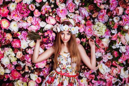 Una hermosa joven con el ramo de flores cerca de una pared floral.
